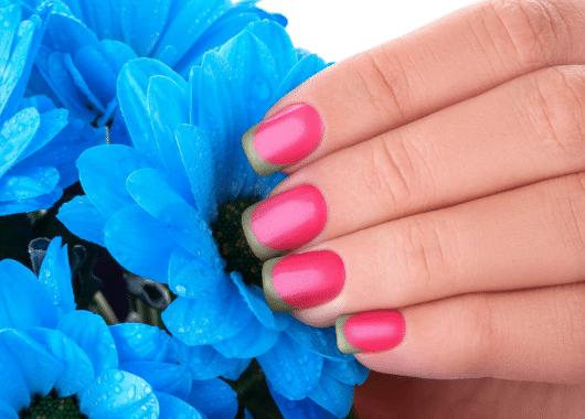 יד עם לק ורוד מחזיקה פרח