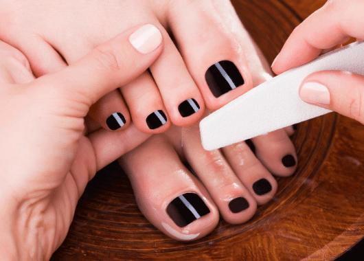 טיפול בפדיקור לאשה עם לק שחור